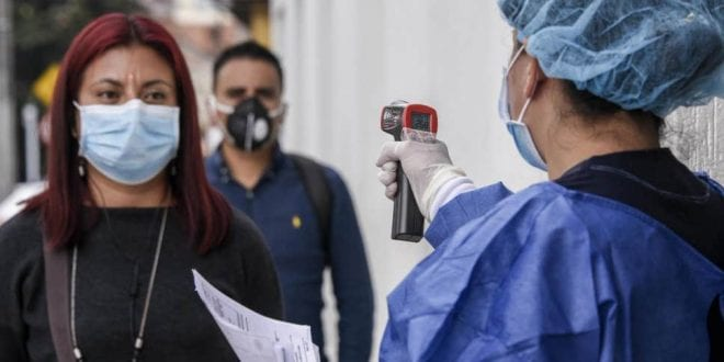Health worker measuring the temparature of a citizen during the COVID-19 pandemic