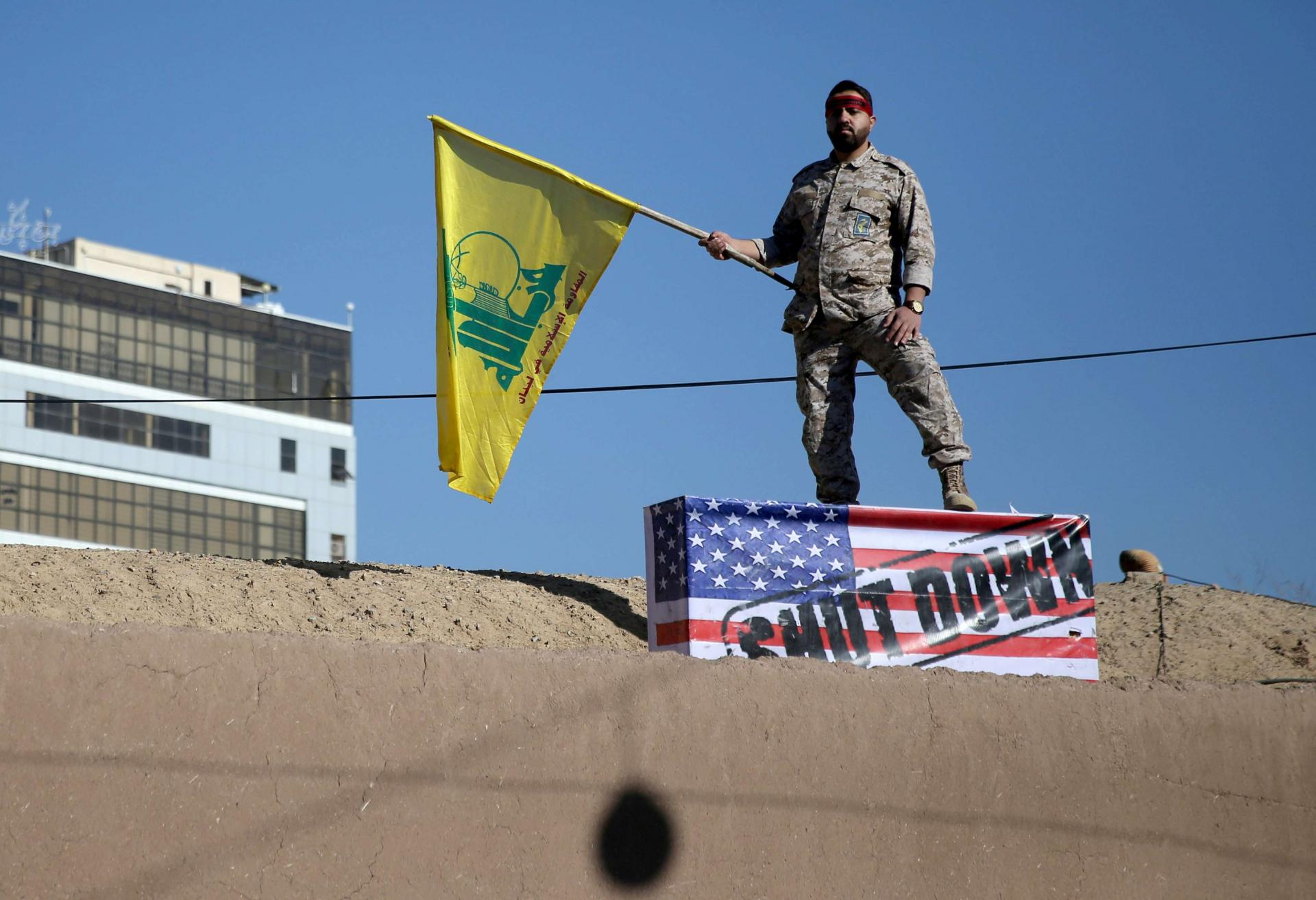 "Iranian soldier holds Hezbollah flag over ""U.S. coffin"""