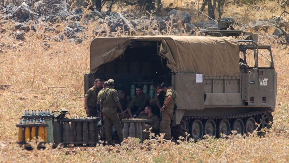 Israeli soldiers behind an armored vehicle