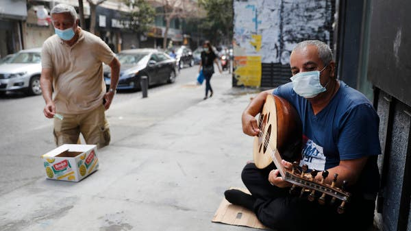 A man wearing a mask plays a musical instrument on a street in Beirut