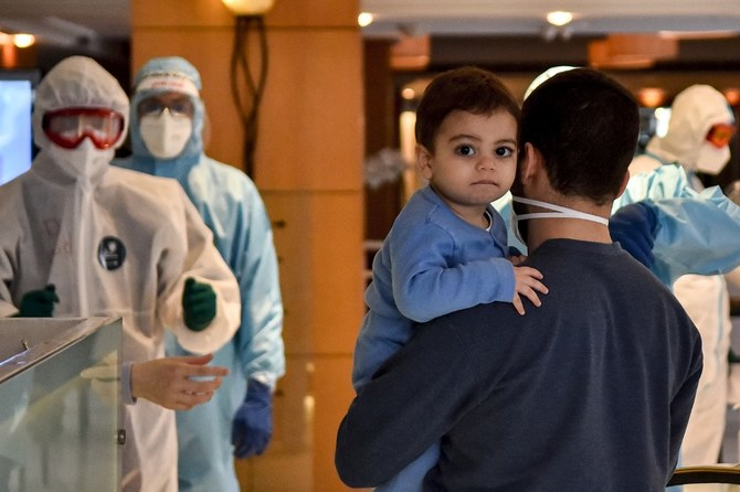 A man carries a child as he arrives in Beirut.