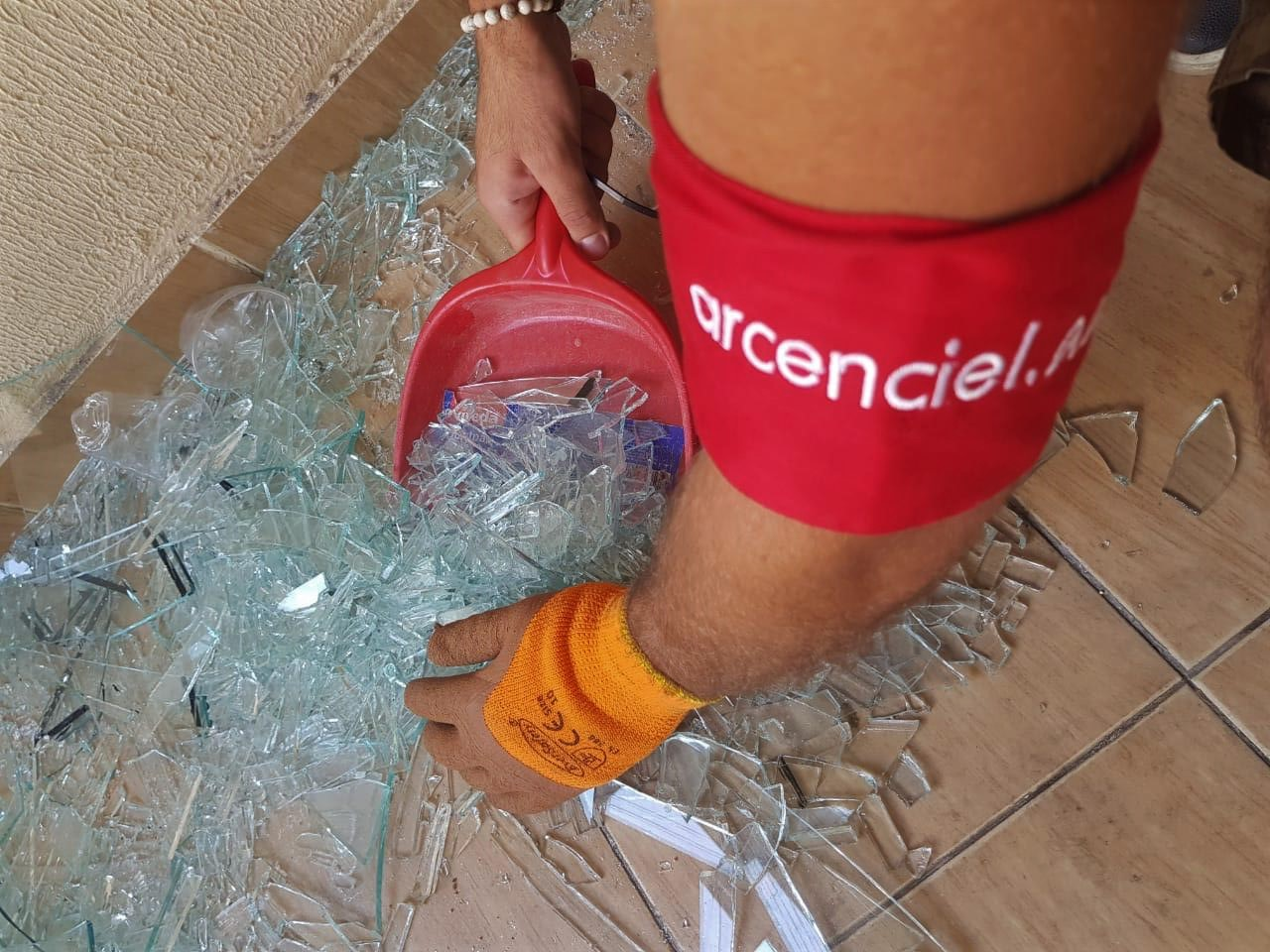 A volunteer collecting glass debris for recycling.