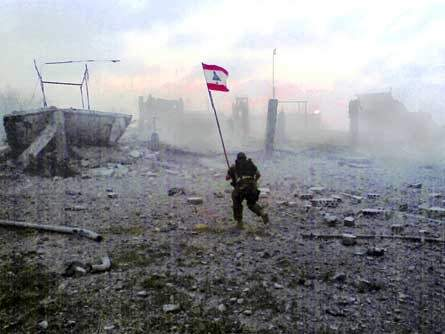 A Lebanese Army soldier holding the Lebanese flag.