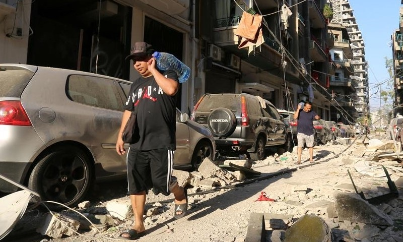 Men carrying bottles of water walk past damaged buildings and vehicles following the August 4th explosion in Beirut.