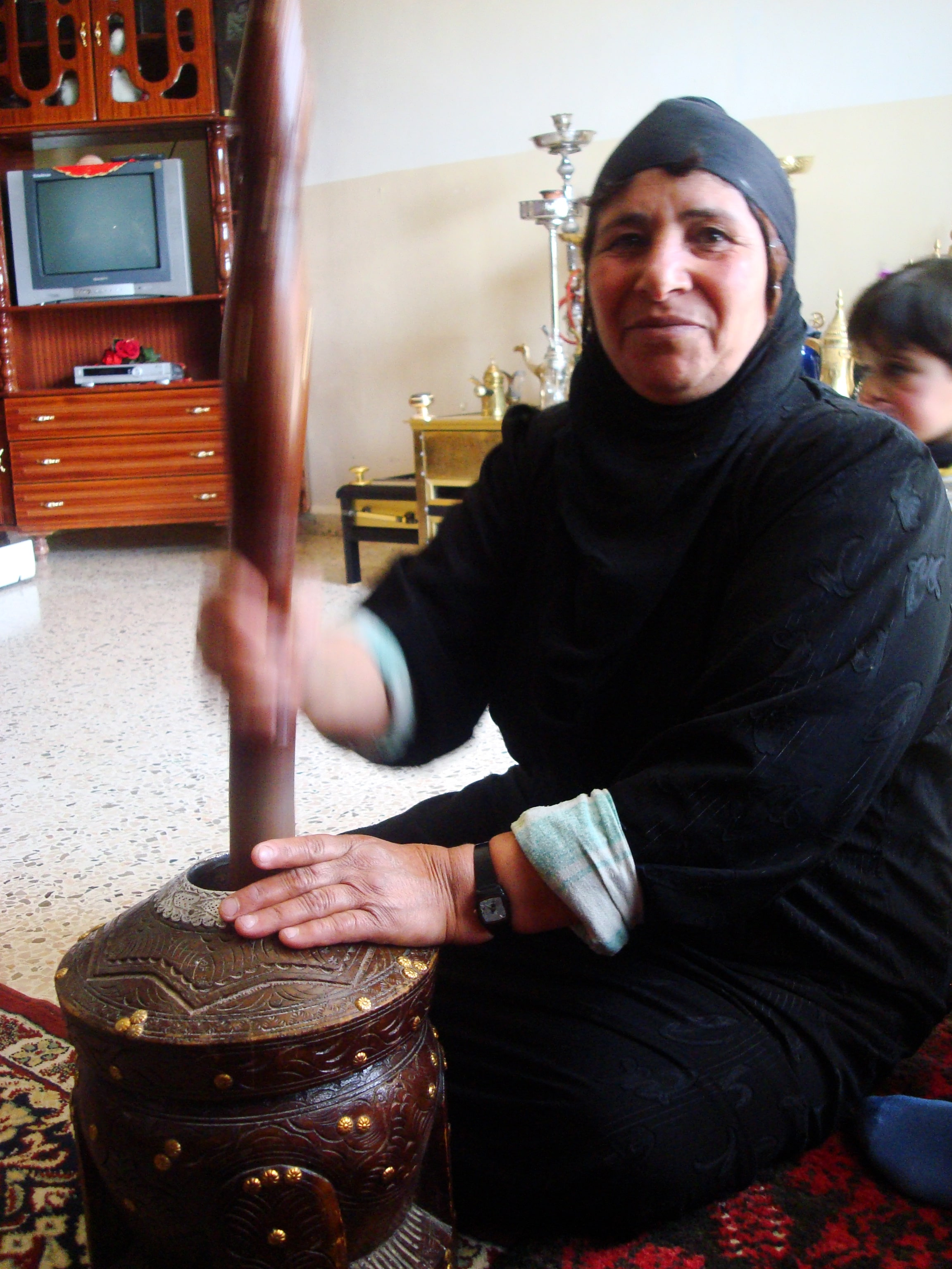 A Bedouin woman beating coffee beans at home.