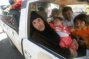 A Lebanese Bedouin woman and her family rejoice as they prepare to cross the Syrian-Lebanese border just hours after a ceasefire came into force on August 14th, 2006.