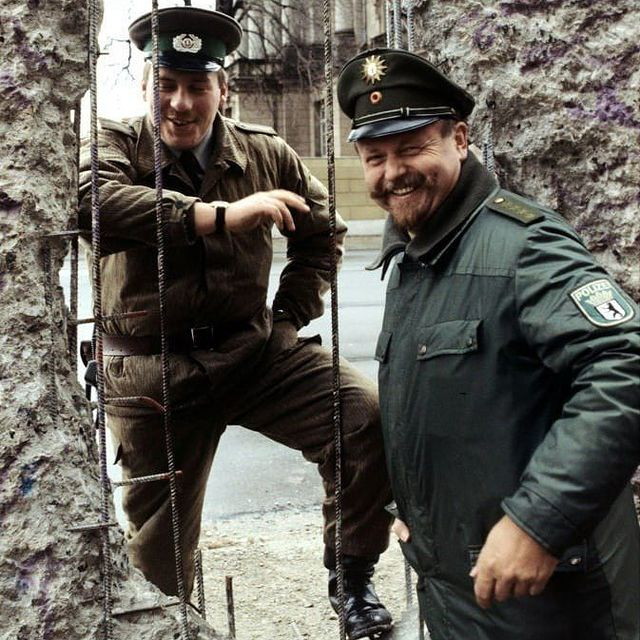 A border guard of the German Democratic Republic and a policeman of the Federal Republic of Germany at the Berlin Wall 1990