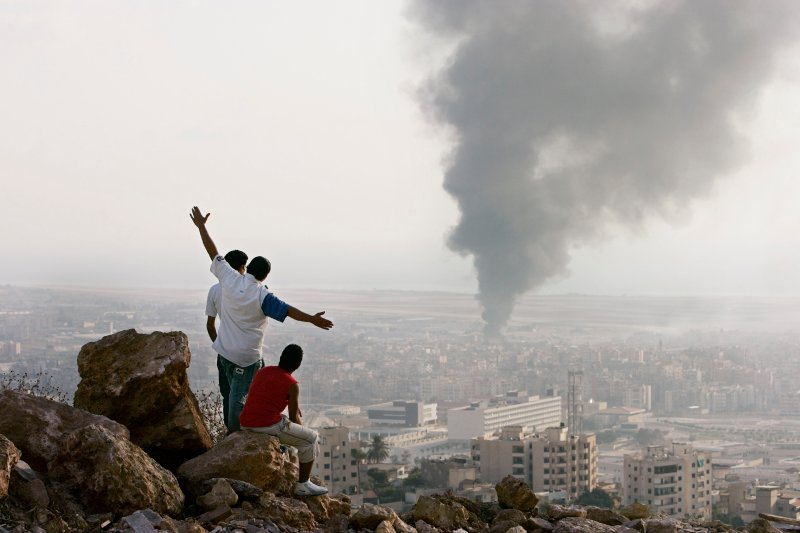 Lebanese teens watch Israeli airstrikes from a hilltop overlooking Beirut at the start of the 2006 War.